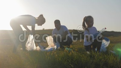 Familia de voluntarios recogiendo basura y plásticos limpiando el parque con una bolsa de basura Trabajo en equipo y ecología almacen de metraje de vídeo
