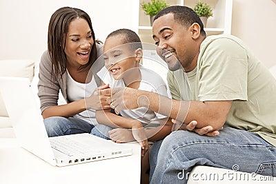 Familia del afroamericano usando el ordenador portátil