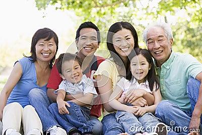 Familia Extensa Que Sienta Al Aire Libre La Sonrisa