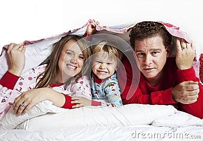 Familia feliz bajo la manta