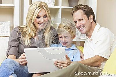 Familia feliz que se sienta en el sofá usando el ordenador portátil