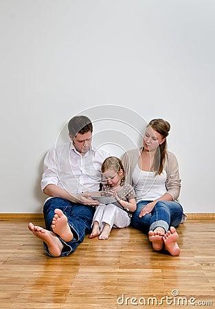 Familia feliz usando el ordenador de la tablilla