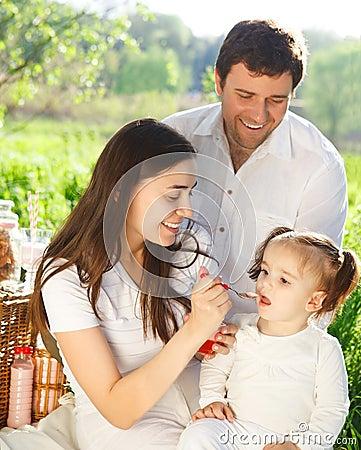 Familia joven feliz con el bebé en una comida campestre
