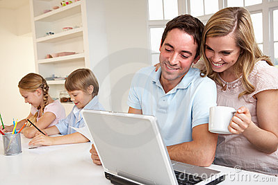 Familia joven feliz que mira y que lee una computadora portátil