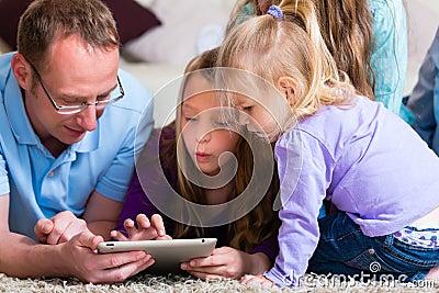 Familia que juega con el ordenador de la tablilla en el país