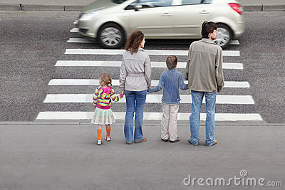Familia que se coloca cerca del paso de peatones