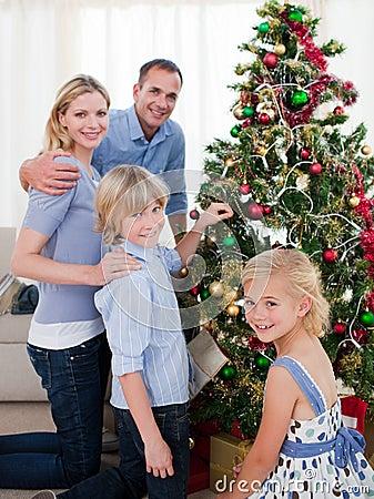 Familia sonriente que adorna un árbol de navidad