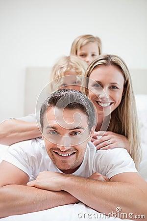 Familia sonriente que miente en cama