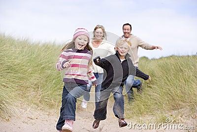 Familie die bij strand het glimlachen loopt