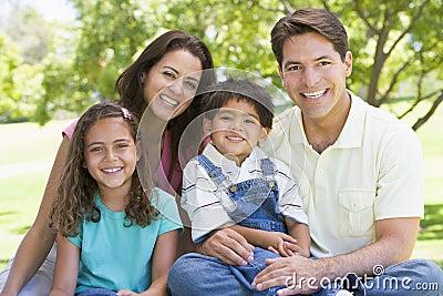 Familie, die draußen lächeln sitzt