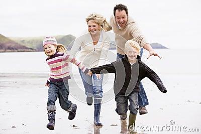 Familie die op de handen van de strandholding loopt