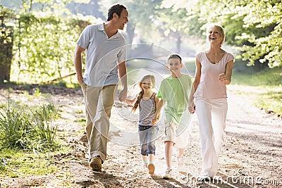 Familie die in openlucht het houden van handen en het glimlachen in werking stelt