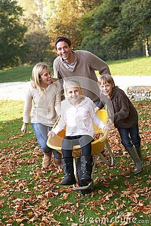 Familie die pret met de herfstbladeren heeft in tuin