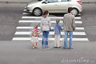Familie die zich dichtbij voetgangersoversteekplaats bevindt