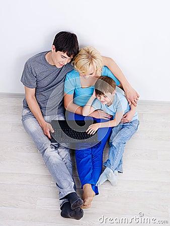 Familie, die zusammen Laptop betrachtet