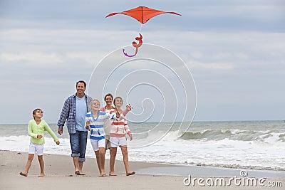 Familie erzieht die Mädchen-Kinder, die Drachen auf Strand fliegen