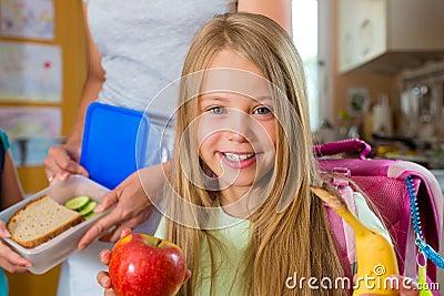 Familie - moeder die ontbijt voor school maakt