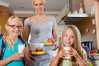 Familie - Mutter, die Frühstück für Schule bildet