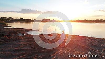 Familievrije tijd - een vader en zijn zoon in paar kleden het lopen bij de visserij op de de holdingshanden van het rivierstrand  stock video