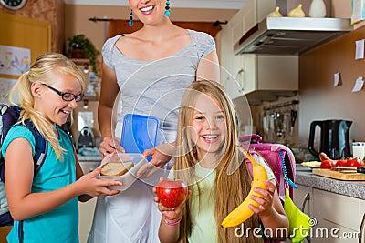 Familj - moder som gör frukosten för skola