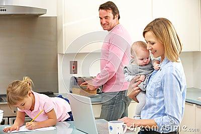 Familj som är upptagen tillsammans i kök