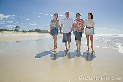 Familj som går på strandholdinghänder