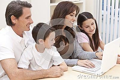 Familj som har den roliga användande bärbar datordatoren hemma