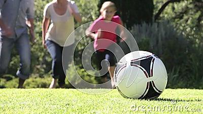 Familjspring som sparkar fotboll i trädgård stock video