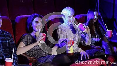 Famille amicale avec intérêt à regarder un film et à manger du pop-corn dans le cinéma banque de vidéos