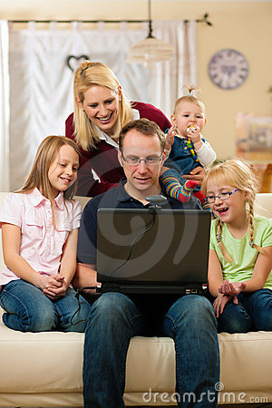 Famille devant l ordinateur ayant le conferenc visuel