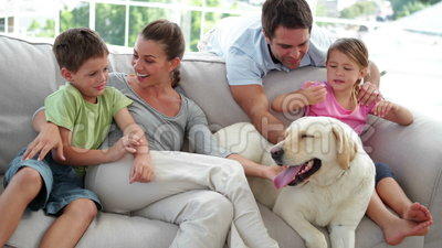 Famille mignonne détendant ensemble sur le divan avec leur chien