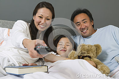 Famille regardant la TV ensemble dans le lit