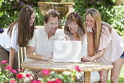 Famille utilisant l ordinateur portable à l extérieur dans le jardin