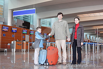 Family in airport hall with suitcases full bod