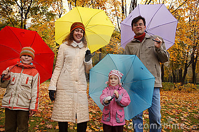 Family in autumn park with coloured umbrellas