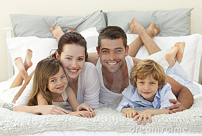 Family in bed smiling at the camera