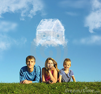 Family with boy on grass and dream cloud house