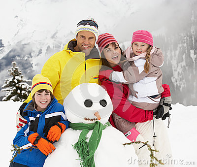 Family Building Snowman On Ski Holiday
