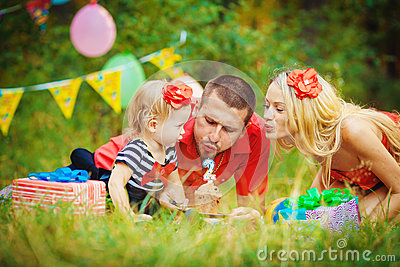 Family celebrating birthday party in green park outdoors
