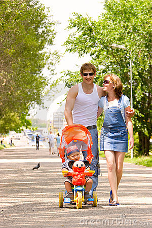 Family with child in stroller walking across park