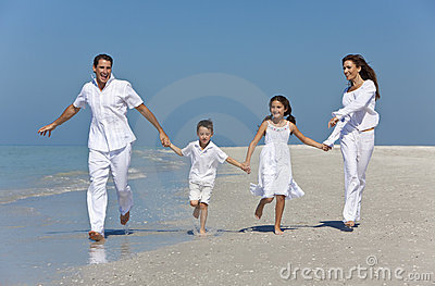 Family With Children Running Having Fun At Beach