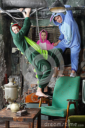 Family in colorful costumes of dragons play in very old room