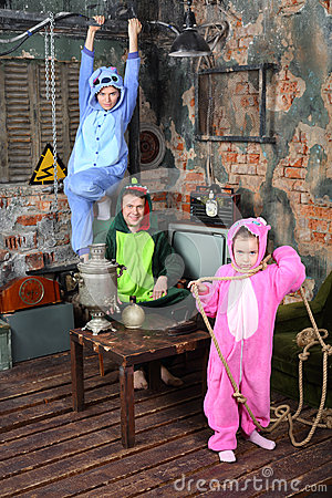 Family in colorful costumes of dragons pose in very old room