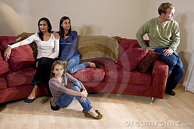 Family on couch with father sitting apart