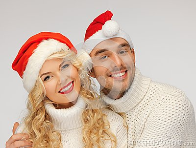 Family couple in sweaters and santa s hats