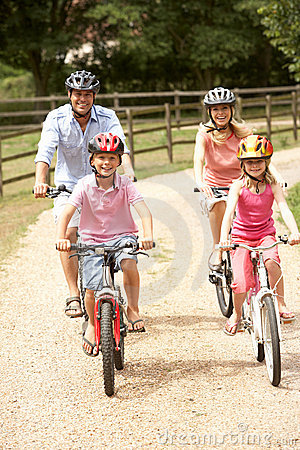 Family Cycling In Countryside Wearing Safety Helme