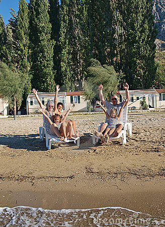 Family on deck chairs at sand beach 2