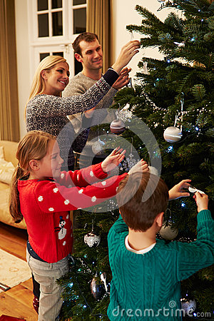 Family Decorating Christmas Tree At Home Together