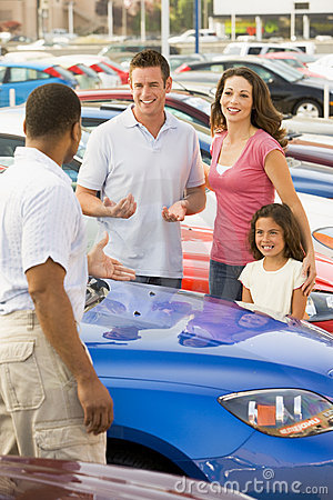 Family discussing new car with salesman