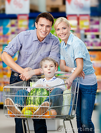 Family drives shopping trolley with food and boy sitting there